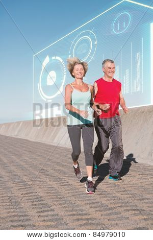 Active senior couple out for a jog against fitness interface