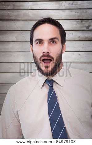 Portrait of shocked businessman with mouth open against wooden planks