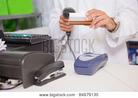 Pharmacist using machine and holding medicine in the pharmacy