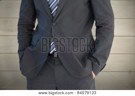 Businessman standing with hand in pocket against bleached wooden planks background
