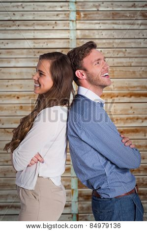 Happy young couple standing back to back against wooden background in pale wood