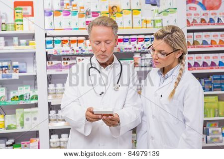 Pharmacist speaking with his trainee about medicine in the pharmacy