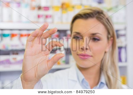Smiling student in lab coat holding pill in the pharmacy
