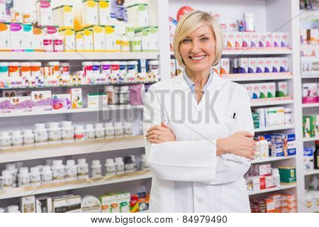 Blonde pharmacist with arms crossed smiling at camera in the pharmacy