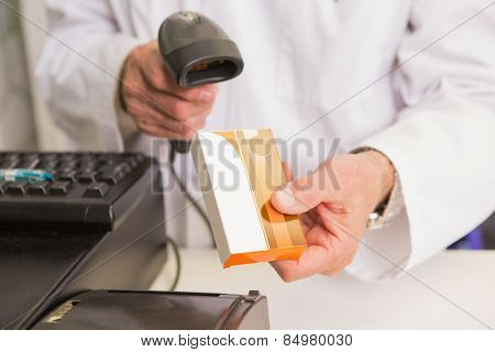 Pharmacist scanning medication with a scanner in the pharmacy