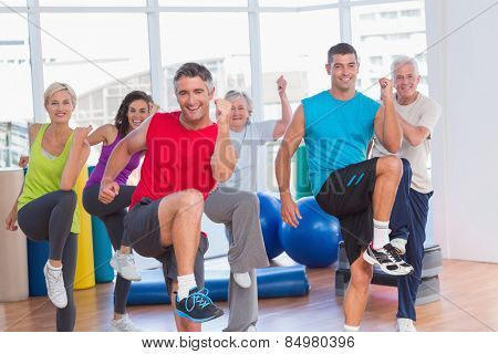 Portrait of fit people performing aerobics exercise in gym class