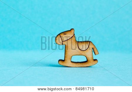 Wooden Icon Of Children's Rocking Horse On Blue Background