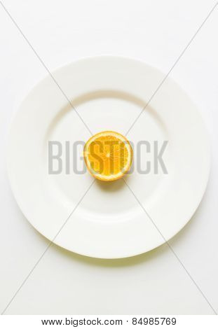 One Half Of Sliced Orange On A White Round Plate On A White Background
