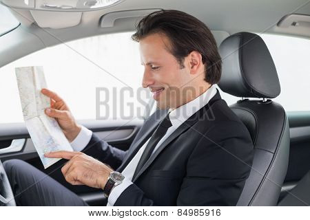 Businessman reading a map in his car