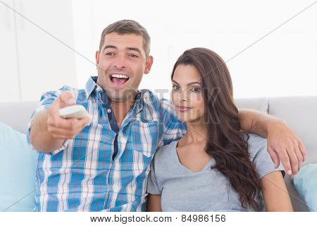 Man changing channels while sitting with woman at home