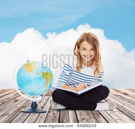 education, geography, childhood, people and school concept - little student girl studying with globe and book over blue sky and cloud background
