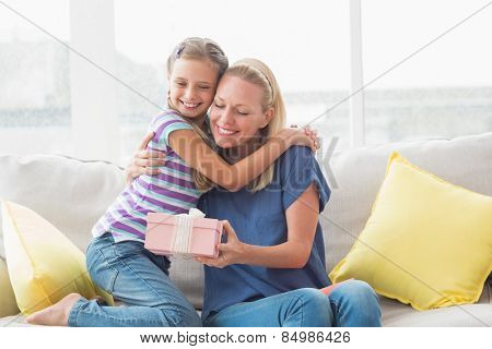 Portrait of happy mother with gift embracing daughter in house