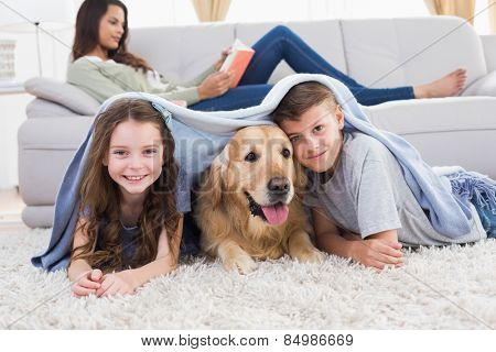 Portrait of happy siblings with dog under blanket at home