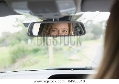 Young woman in the drivers seat looking in the mirror in her car