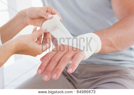 Doctor bandaging her patient hand in medical office