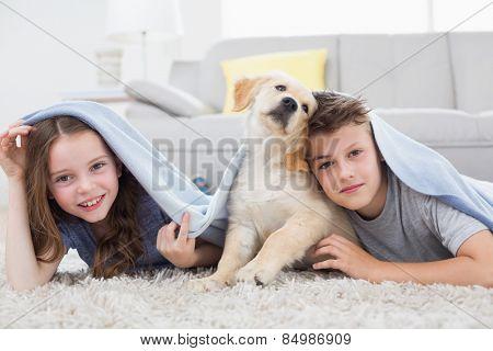 Portrait of cute siblings with dog under blanket in living room