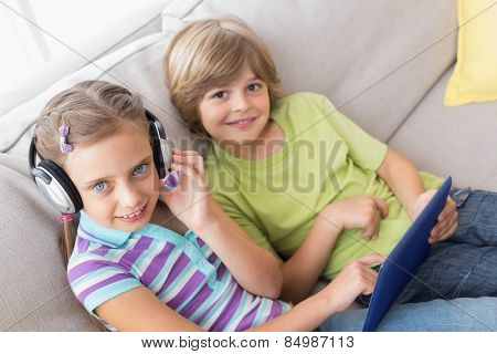 Portrait of siblings using digital tablet while listening music on sofa at home