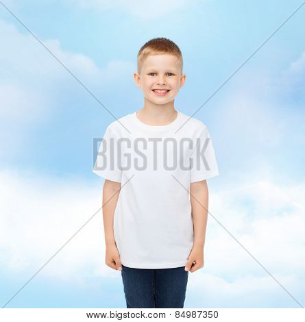 advertising, dream, people and childhood concept - smiling little boy in white blank t-shirt over cloudy sky background