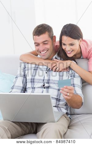 Happy couple shopping online through laptop using debit card at home