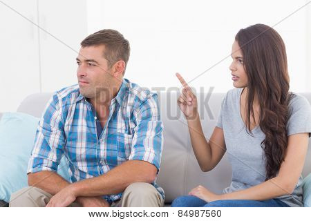 Angry young woman arguing with man while sitting on sofa at home