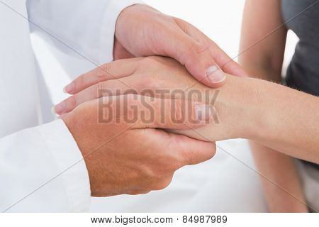 Doctor examining his patient hand in medical office
