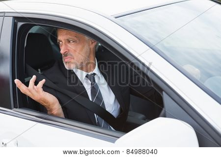 Perplexed businessman in the drivers seat in his car