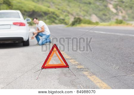 Man changing wheel after a car breakdown at the side of the road