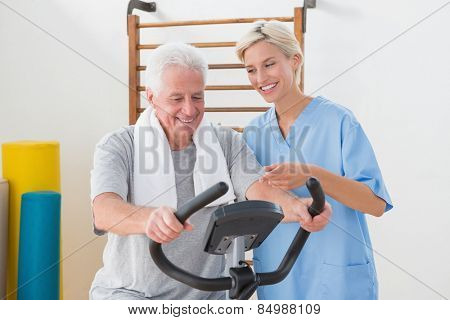 Senior man doing exercise bike with therapist in fitness studio