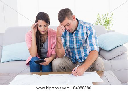 Worried couple calculating home finances at table in house