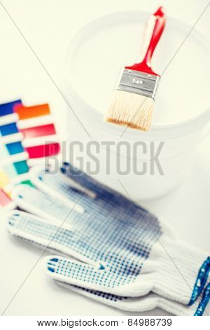 interior design and home renovation concept - paintbrush, paint pot, gloves and pantone samples