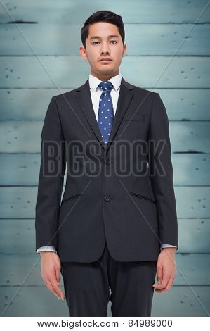 Stern businessman looking at camera against wooden planks
