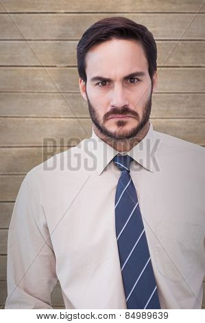 Portrait of an angry businessman against wooden planks
