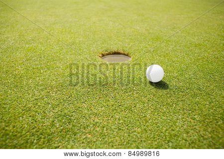Golf ball near hole on a sunny day at the golf course