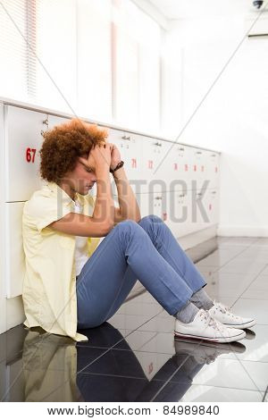 Side view of tensed young man sitting in office corridor