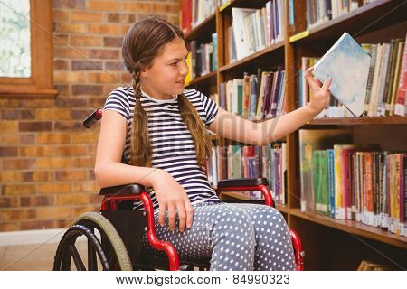 Cute little girl in wheelchair selecting book in the library