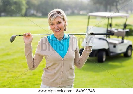 Cheerful golfer standing on the putting green on a sunny day at the golf course