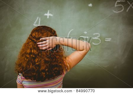 Rear view of little girl looking at blackboard in the classroom
