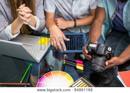 Close up of creative business people with digital camera at office desk