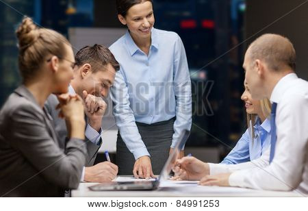 business, technology, people, deadline and team work concept - smiling female boss talking to business group at night office background
