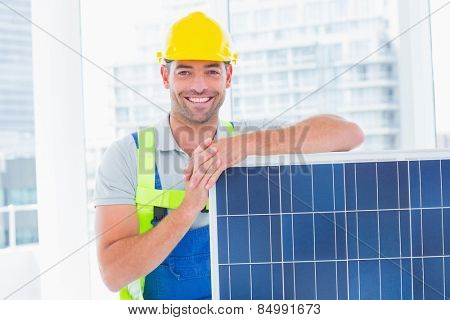 Portrait of happy handyman with solar panel in bright office