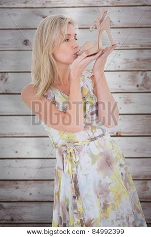 Elegant blonde admiring a shoe against wooden planks