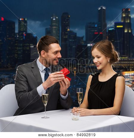 celebration, , holidays and people concept - smiling couple with red gift box at restaurant over night city background