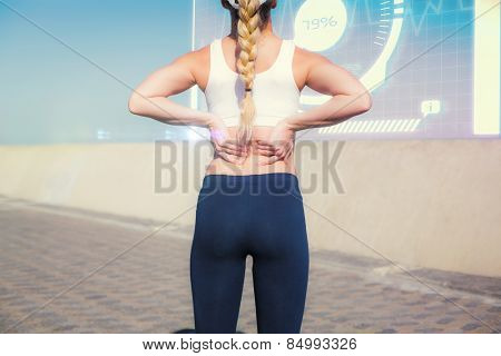 Fit blonde touching her back on the pier against fitness interface