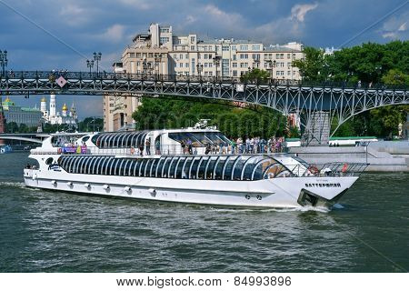 MOSCOW, RUSSIA - JULY 6, 2014: People traveling on the yacht of Flotilla Radisson Royal near the Patriarch bridge. Working all year round, the Flotilla carry half million passengers per year