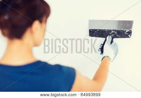interior design and home renovation concept - woman plastering the wall with trowel
