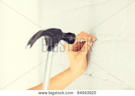 architecture and home renovation concept - architect hammering nail in wall