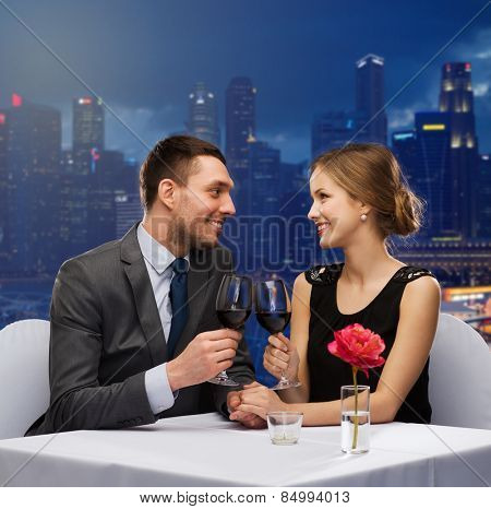 holidays, celebration, dating and people concept - smiling couple clinking glasses of champagne and looking to each other at restaurant over night city background