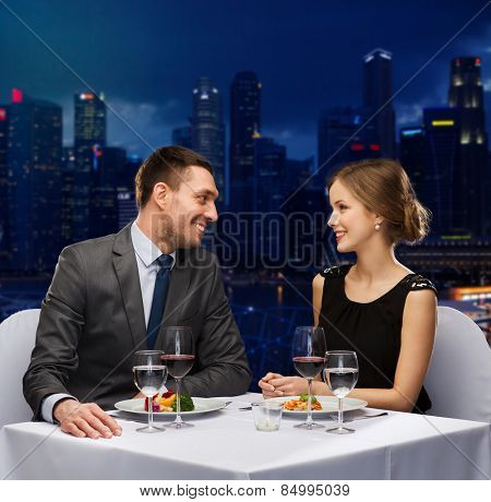 people, celebration, romantic and holidays concept - smiling couple with red wine and food talking at restaurant over night city background