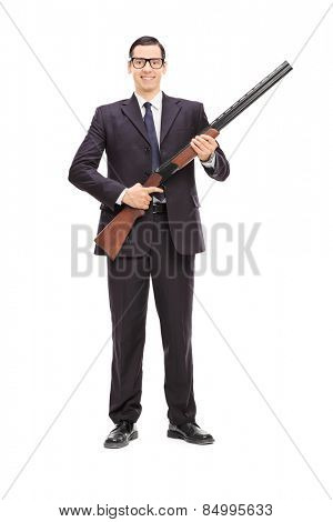 Full length portrait of a male bodyguard holding a shotgun isolated on white background