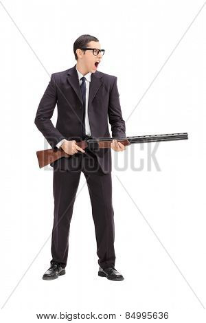 Full length portrait of an angry man holding a rifle and shouting isolated on white background